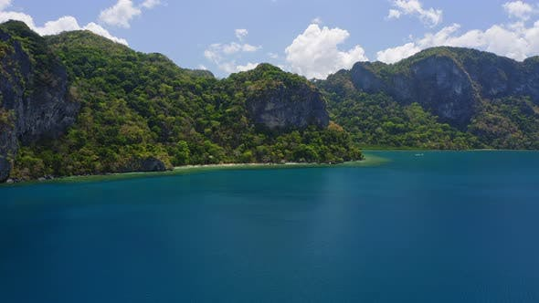 Thumbnail for Aerial Fly Approaching Uninhabitable Jungle Lagen Island. El Nido, Palawan, Philippines. Deep Blue