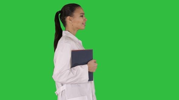 Thumbnail for Happy smiling female doctor walking holding notebooks