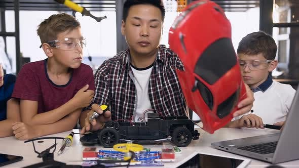 Thumbnail for Three Boys with Teacher of Electronics Engineer Using Screwdriver to Disassemble Robotic Machine