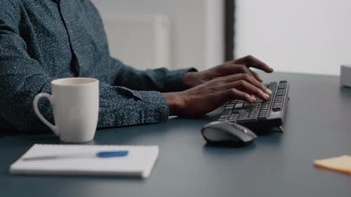 Close Up of African American Man Hands Typing on Computer Keyboard