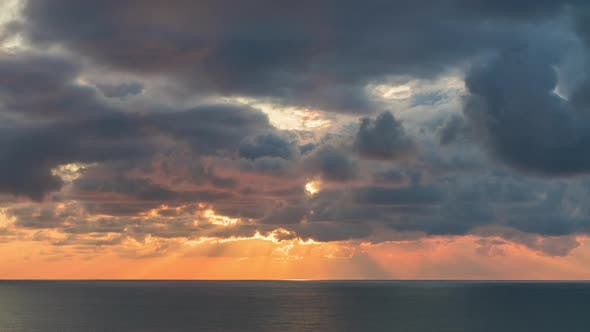 Thumbnail for Clouds Crossing Sky Over the Sea Horizon at Sunset with Sun Rays Emerge Through the Storm Clouds