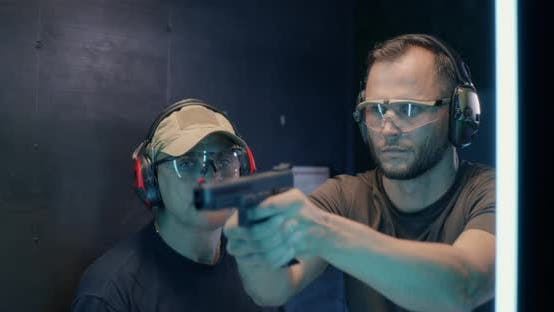 Thumbnail for Mature Instructor Teaching Man To Shoot Pistol