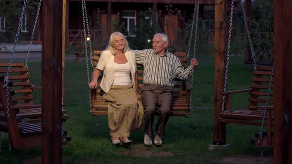 Couple Sitting on Porch Swing.