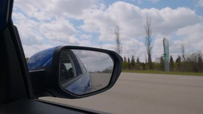 Mirror of a Car Moving on a Highway