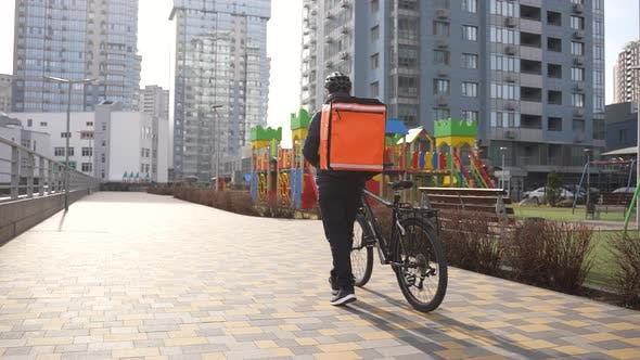 Food Courier Walking with Thermal Bag and Bike