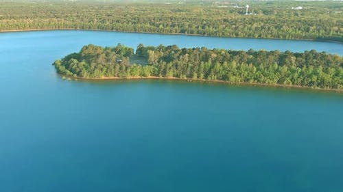 Beautiful spring nature landscape with a blue lake water between green forest