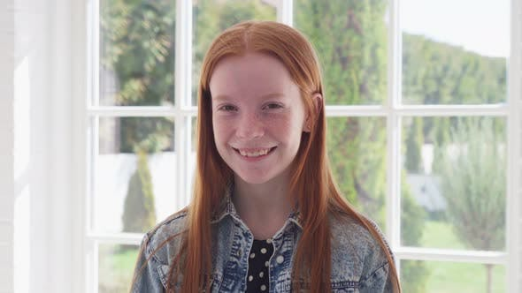 Happy Ginger Girl with Freckles Smiling Against White Window