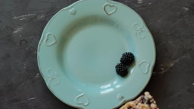 Piece of cake with blackberries and ice cream on a blue plate