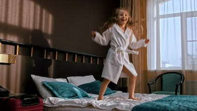 A Little Girl with Long Hair Jumping on the Bed of the Hotel Room