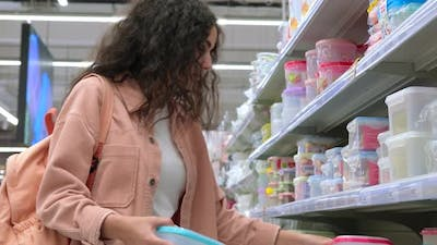 Woman Choosing Plastic Boxes for Food in the Store