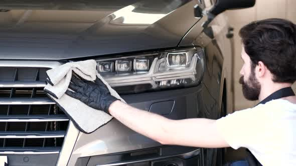 Man Wipes a Car in a Garage