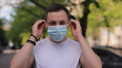 Man Putting on Surgical Mask in a City