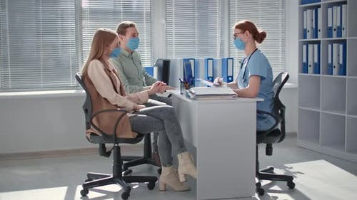Couple Wearing Medical Masks to Protect Against Virus in Doctor Office Undergo Medical Examinations