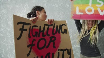 Positive Girls with Dreadlocks are Holding LGBTQ Posters