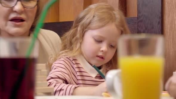 Thumbnail for Loving Grandparents Having Family Dinner with Granddaughter