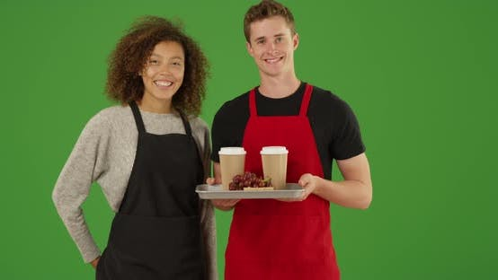 Thumbnail for Portrait of two waiters with tray of food and drinks smiling on green screen