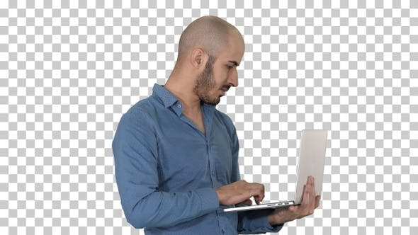 Young middle eastern businessman standing and typing on laptop
