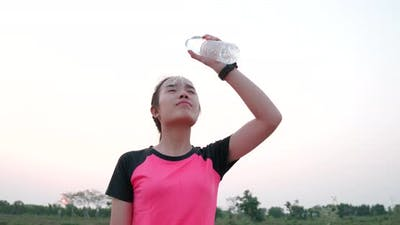 Young woman cooling herself with water after workout