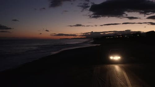 Jeep off road on the beach at the sunset