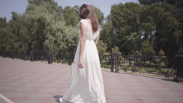 Cover Image for Beautiful Young Girl Wearing Sunglasses and a Long White Summer Fashion Dress Walking Through