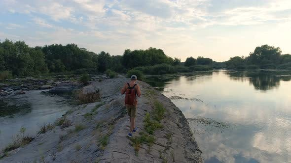 Young Man Walking on Riverbank
