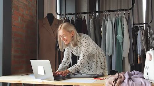 Happy Tailor in Workplace Uses Laptop To Sign Lucrative Contract