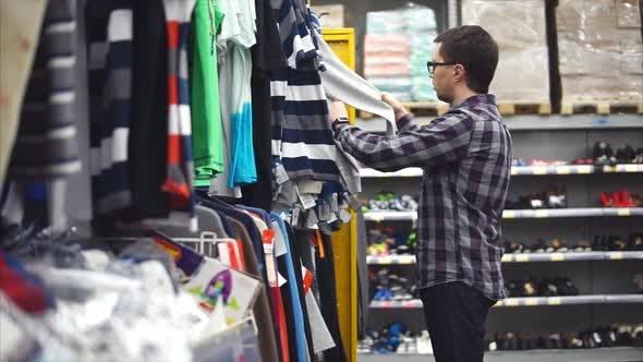 Mann im Einkaufszentrum wählt Kleidung