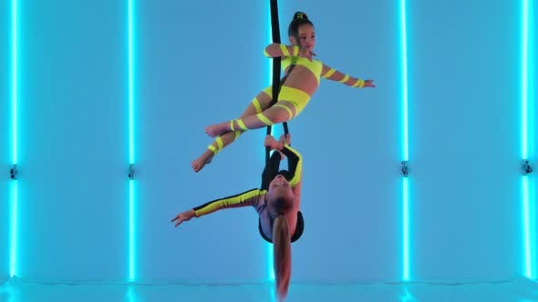 Thumbnail for Two Young Circus Performers Rotate on an Air Hoop