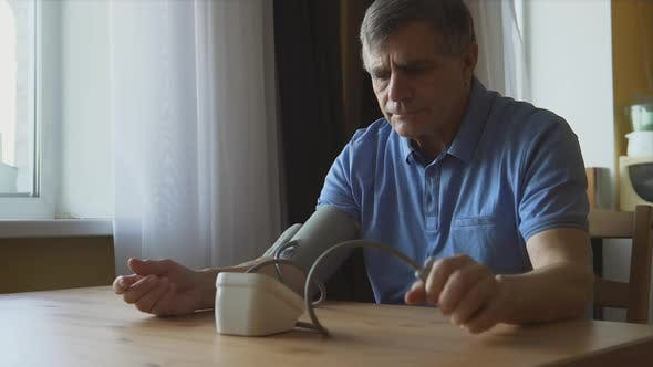 Thumbnail for An elderly man measuring the blood pressure at home