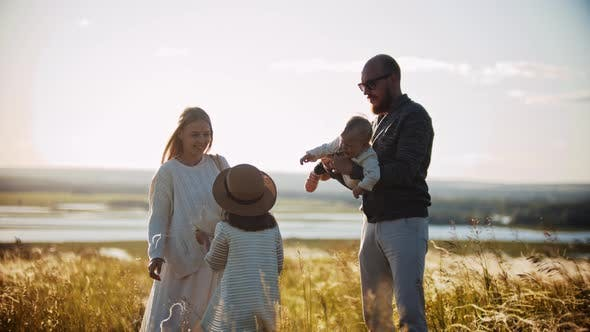 Thumbnail for Young Family Standing on the Wheat Field - Father Holding a Little Baby on His Hands and Little Girl