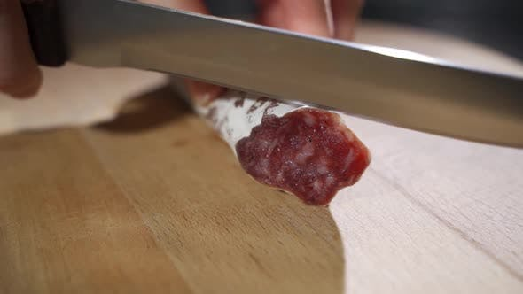 An Experienced Chef in a Professional Kitchen Cuts the Seasoned Italian Salami Sausage Is Cut with a