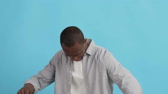 Positive African American Guy Dancing, Blue Studio Background