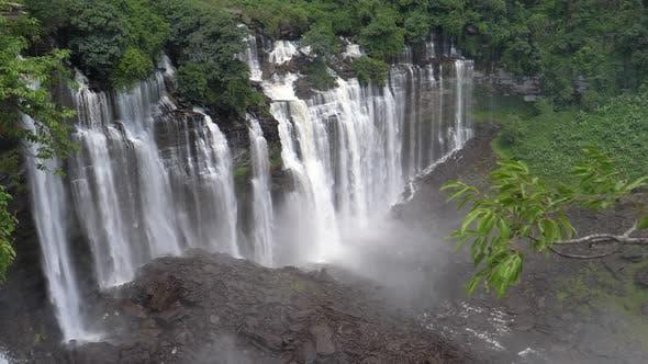 Thumbnail for Kalandula Falls sprühen Wasser über Büsche und herbenartige Felsen in Angola