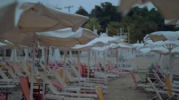 Thumbnail for Empty Sunbeds Under Umbrellas on Resort in Windy Evening