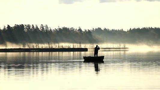 Spin Fishing From Wooden Boat In The Fog