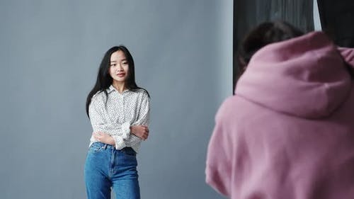 Woman Photographer with the Professional Camera Shooting Asian Korean Model