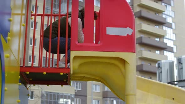 Thumbnail for Young Boy Enjoying Playground Slide with Mom and Dad