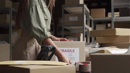 Female Post Mail Storage Worker Holding Tape Dispenser Sealing Shipping Box