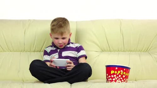 Teenager Plays on Smartphone Online Game, Eats Popcorn. Slow Motion
