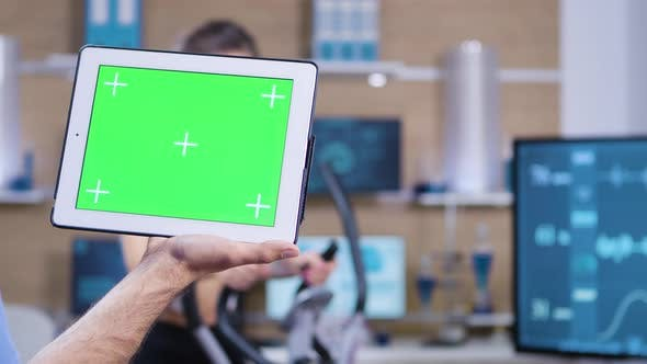 Thumbnail for Dolly Shot of Doctor in Sport Science Holding Tablet with Green Screen