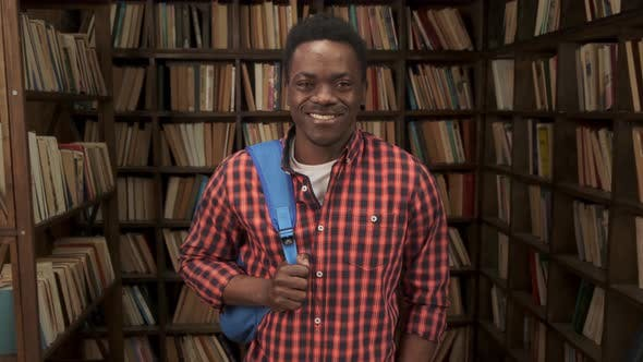 African American Student Holding Backpack in University or High School Library Smiling Looking at