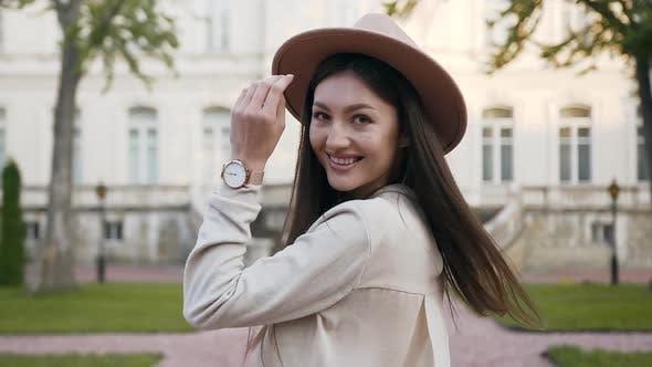 Thumbnail for Frau mit langen Haaren und Mode Hut, die Drehen und Blick auf die Kamera beim Gehen