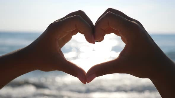 Thumbnail for Woman Making Heart Through Her Hands with Seascape at Background. Close Up of Female Arms Showing