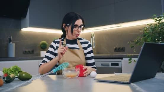 Brünette erklärt ihren Online-Gesprächspartner Wie man Omelett mit Gemüse zubereitet