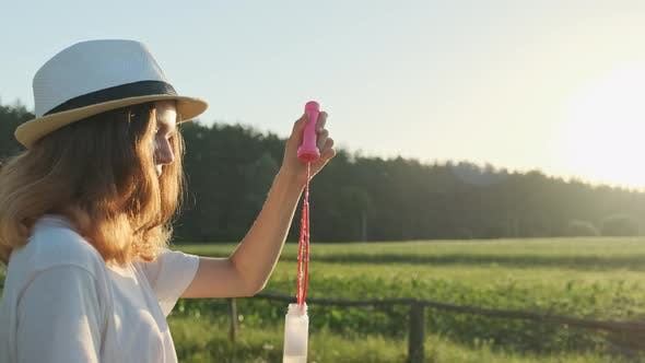Thumbnail for Beautiful Girl Teenager in a Hat Blowing Soap Bubbles