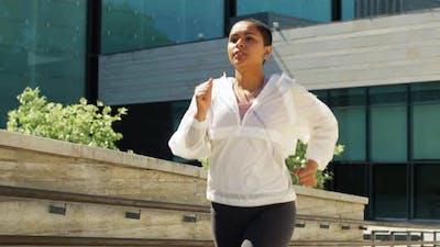 African American Woman with Earphones Running