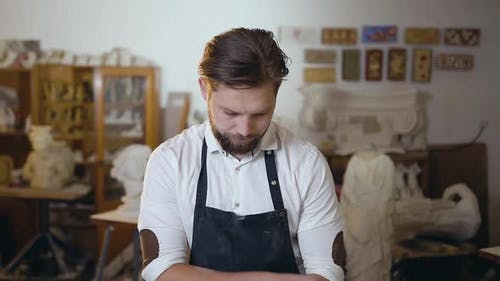 Master in white Shirt and Apron Standing with Folded Hands and Looking at Camera