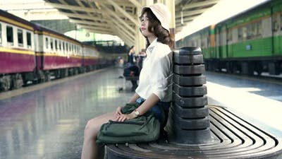 Asian woman waiting the train at train station for travel in summer.