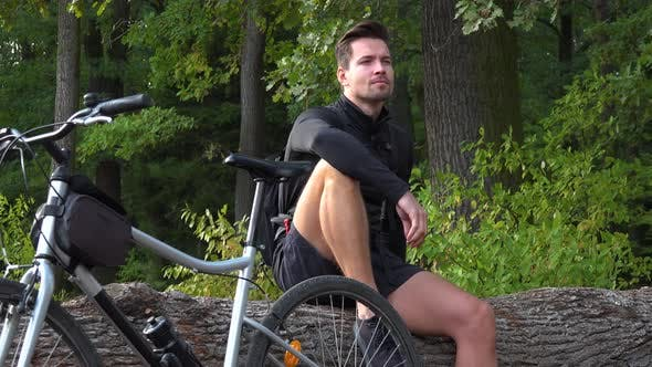 Thumbnail for A Young Handsome Cyclist Sits on a Log Next To His Bike in a Forest and Looks Around