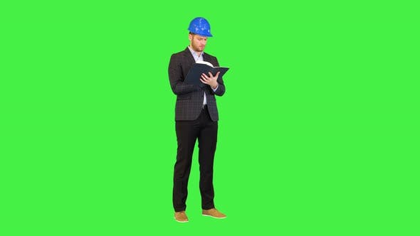 Concentrated Architect or Male Designer in Protective Construction Helmet Make Notes in Notebook on